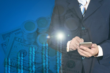 Double exposure businessman using smart phone on stack of coins.