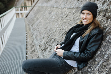Smiling woman sitting on wall