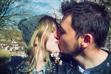 Pareja joven besándose mientras se hacen una foto