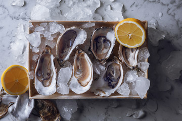 Oyster box with ice and lemon over a gray marble table