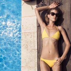 Young slim beautiful woman in yellow bikini sunbathing near swimming pool.