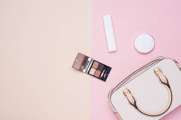 Flat lay of female fashion accessories and white handbag on pastel color background with copyspace