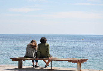 Young couple of people sitting on a bench and looking at the sea