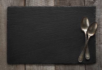 Black slate plate and vintage spoons on wooden board. Top view. Space for your text.