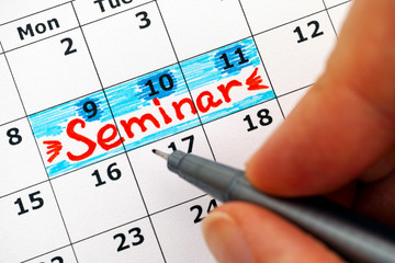 Woman fingers with pen writing reminder Seminar in calendar