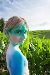 Mädchen mit blauem Bodypainting im Freien