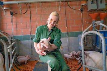 Junge Landwirtin im Schweinstall stolz mit Ferkel auf dem Arm