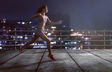 Läuferin joggt vor beleuchteter Stadt