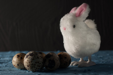 Easter rabbits,quail eggs on blue background. close up