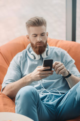 Young man with headphones sitting in bean bag chair and using smartphone