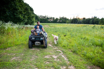 Father and son driving all terrain vehicle in field with dog