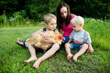 Mother and sons sitting on grass, holding chicken