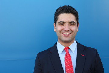 Happy ethnic businessman on blue background