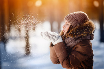 Close-up portrait of a young beautiful happy smiling girl wearing a stylish knitted winter hat, mittens, scarf yoke. Daylight - sunset and glare. Snowfall. Toned