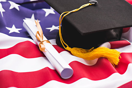 Close-up view of graduation mortarboard and diploma on US flag, education concept