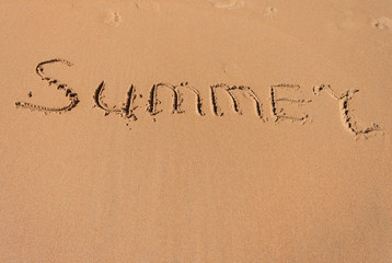 The word summer written in the sand on a beach