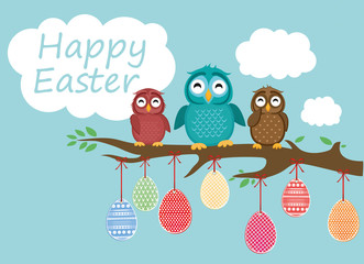 Easter eggs hang on ribbons. Lovely owls are sitting on a tree branch. Greeting card