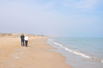 People strolling by the sea on a sunny day