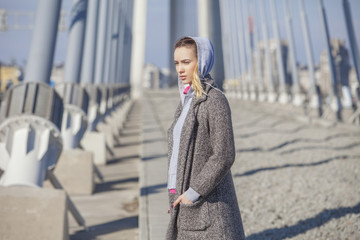 Beautiful young woman standing on the bridge