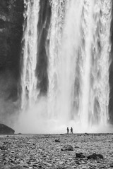 Skogafoss waterfall with two people at the bottom showing the scale of the waterfall in Iceland.