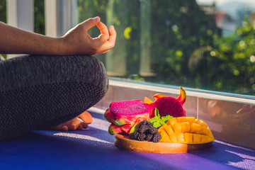 hand of a woman meditating in a yoga pose, sitting in lotus with fruits in front of her dragon fruit, mango and mulberry