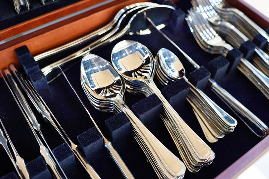 Cutlery forks, spoons and knives on dark blue velvet