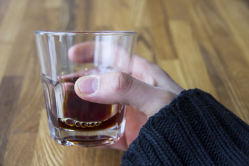 Man's hand holds glass with alcoholic drink. First-person view