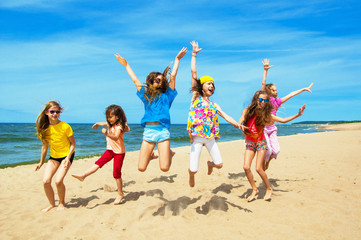 Happy active children jumping on the beach
