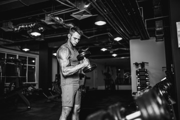 Handsome muscular man is working out and posing with dumbbells at a gym
