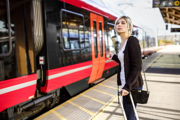 Woman With Luggage Standing At Train Station