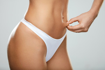 Hot Slim Woman Body In White Panties Pinching Abdomen. Fitness