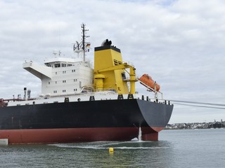 Products Tanker discharging at the Oil Terminal of Lorient, France, with black hull and yellow funnel on a cloudy day. Horizontal stern view
