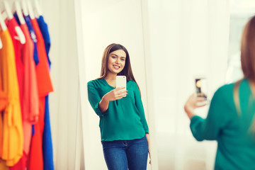 woman with smartphone taking mirror selfie at home