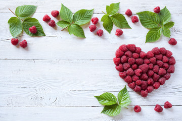 Berries raspberries in a heart shape on wooden background