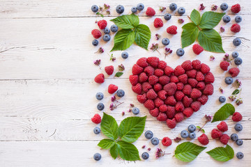 Background with berries raspberries in a heart shape and blueberries