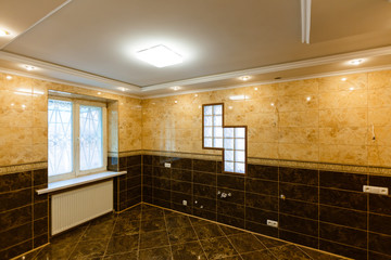 Modern bathroom wall made in dark color tiles which covered the bathtub and towels near the fancy plant