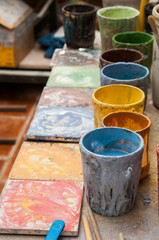 Work table of a pottery decorator in Caltagirone, Sicily, with different color containers and paintbrushes