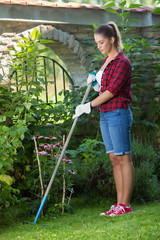 Young woman is working in the garden. She is raking up leaves and grass from the lawn.