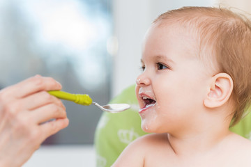 Mothers feeding the baby with cottage cheese