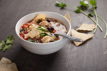 Homemade Taco Soup in small white bowl with crushed tortilla chips on dark wooden background horizontal shot