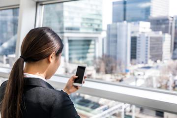 businesswoman looking smart phone screen