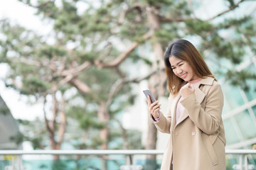Beautiful asian woman checking news on smartphone and celebrate feeling success or happy pose, education or technology or startup business concept tree background and outdoor with copy space.