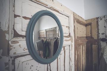 Round mirror hanging on a grunge wooden wall