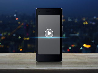 Play button on modern smart phone screen on wooden table over blur colorful night light of city tower, Business music online concept