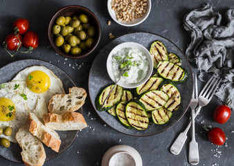 Grilled zucchini, fried eggs, olives, tomatoes, ciabatta - simple snack or appetizer. Mediterranean style food. On a dark background, top view. Flat lay