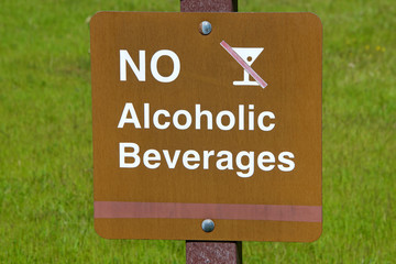 Close up on a warning sign no alcoholic beverages in a public park, green grass background.