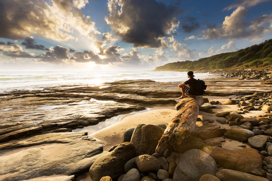 A person sits on a beautiful rocky beach and watches as the sun bursts through the clouds over the sea in this beautiful seascape.