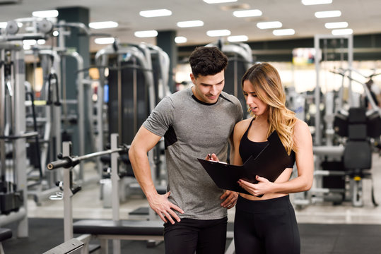 Personal trainer and client looking at his progress at the gym
