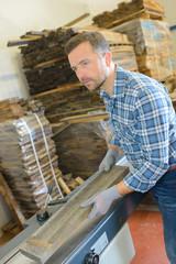 Workman putting wood onto conveyor