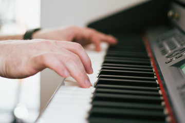 Close-up hands of musician who plays keyboards.